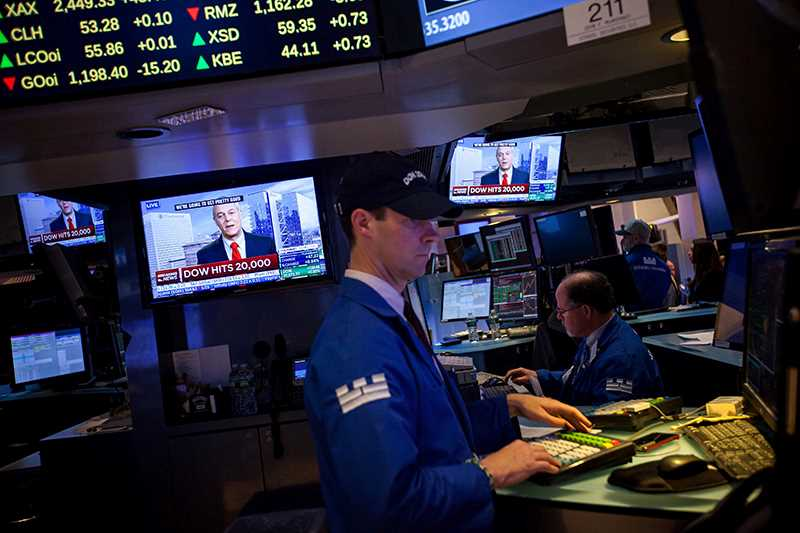 Man in front of screen at stock exchange