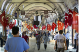People walking in a market with Turkish flags on each side